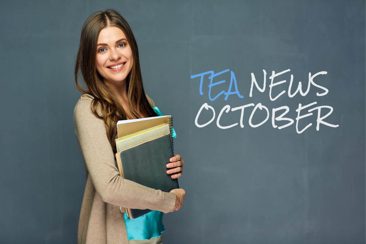Female teacher carrying books in front of blackboard with TEA News October writing