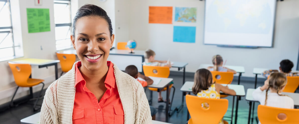 Woman smiling in front of classroom