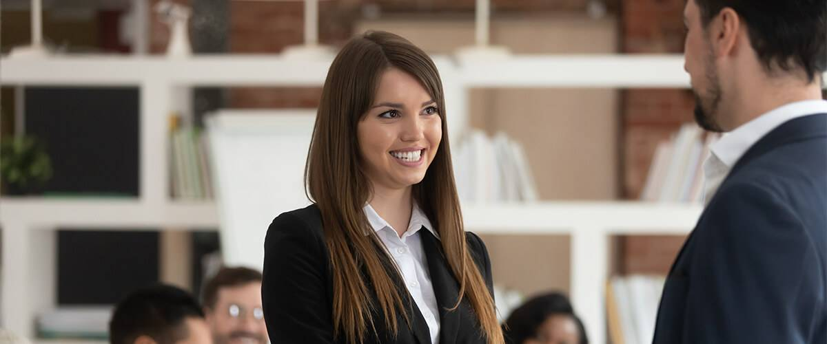 Woman teacher smiling in front of group of teachers