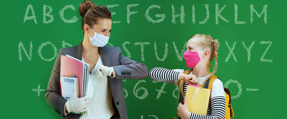 Woman teacher and schoolgirl wearing face-masks and touching elbows